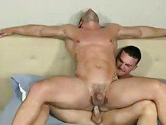 Два гея с мускулистыми телами в кроватке